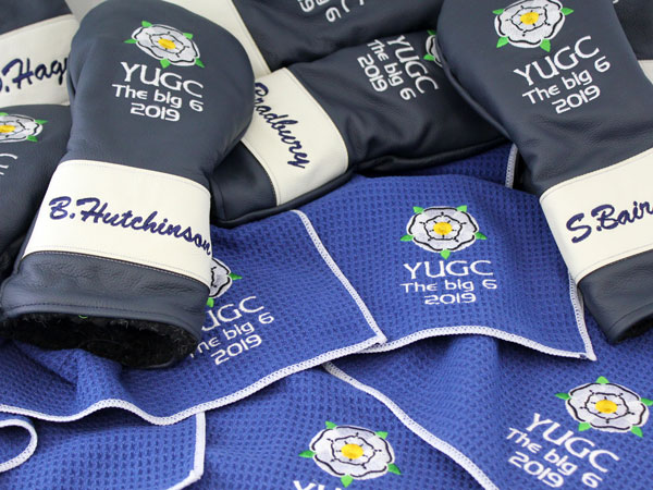 Image of leather headcovers and golf towels together